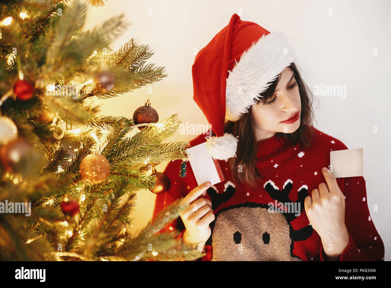 christmas shopping and sales beautiful girl holding two credit cards for discount and buying gifts on background of golden christmas tree with lights