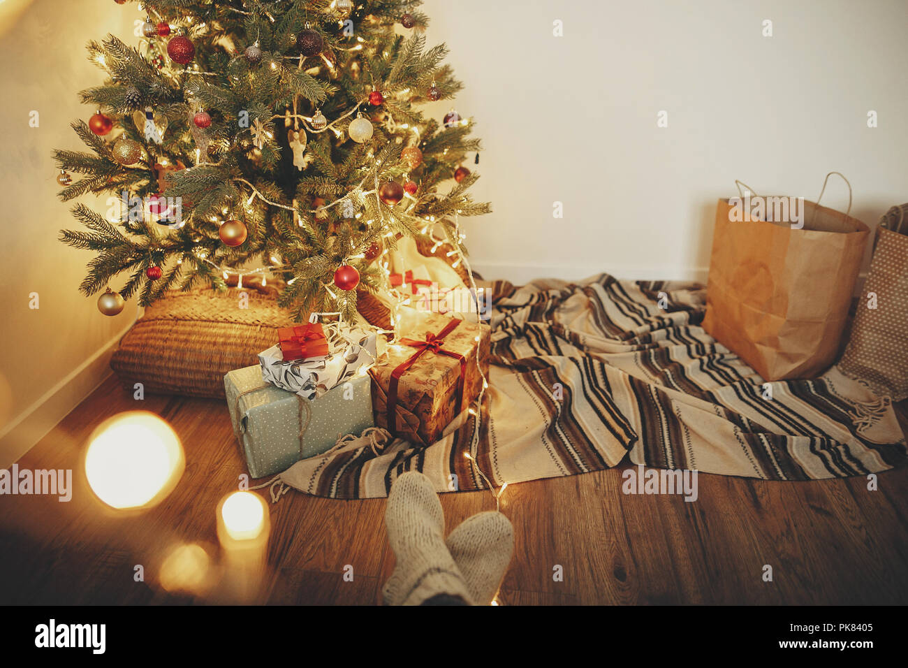 5418b7e5d43 girl legs in stylish warm sock sitting with garland lights at christmas  tree with presents and gifts. socks on rug in festive room. decor for  winter h