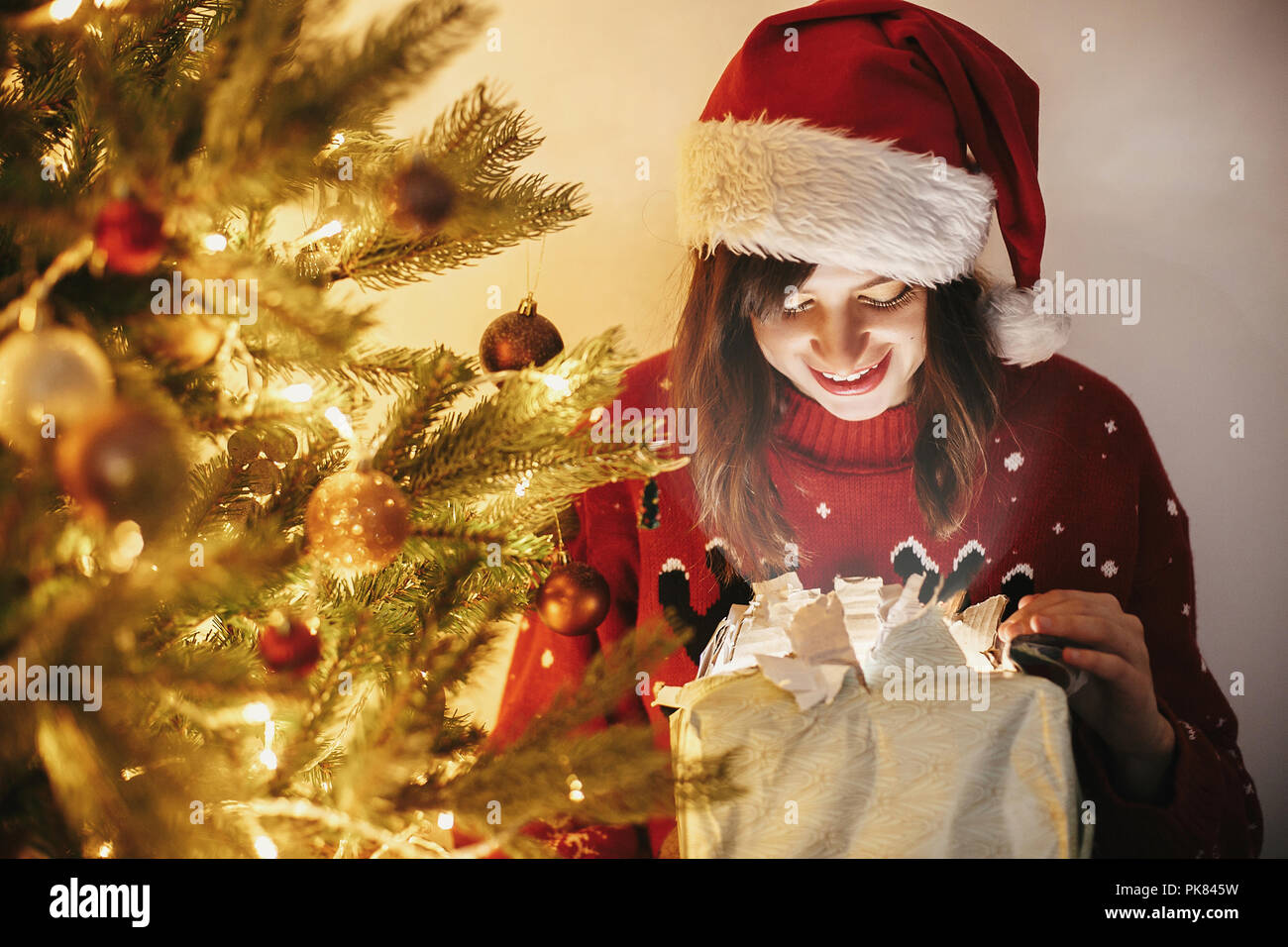 f293d613ed01d happy girl in santa hat opening magic Christmas gift box at golden  beautiful christmas tree with lights and presents in festive room. winter  atmospher