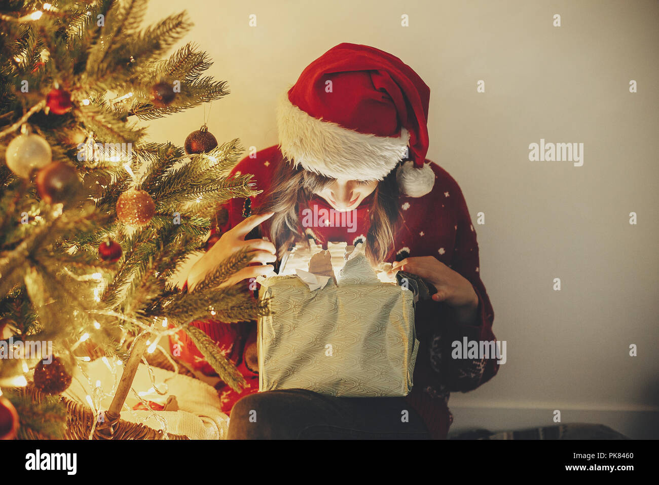 6454fb29f9e2c Merry Christmas. happy girl in santa hat opening magic Christmas gift box  at golden beautiful christmas tree with lights and presents in festive room.