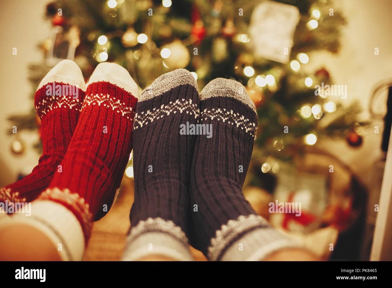 stylish festive socks on couple legs on background of golden ...
