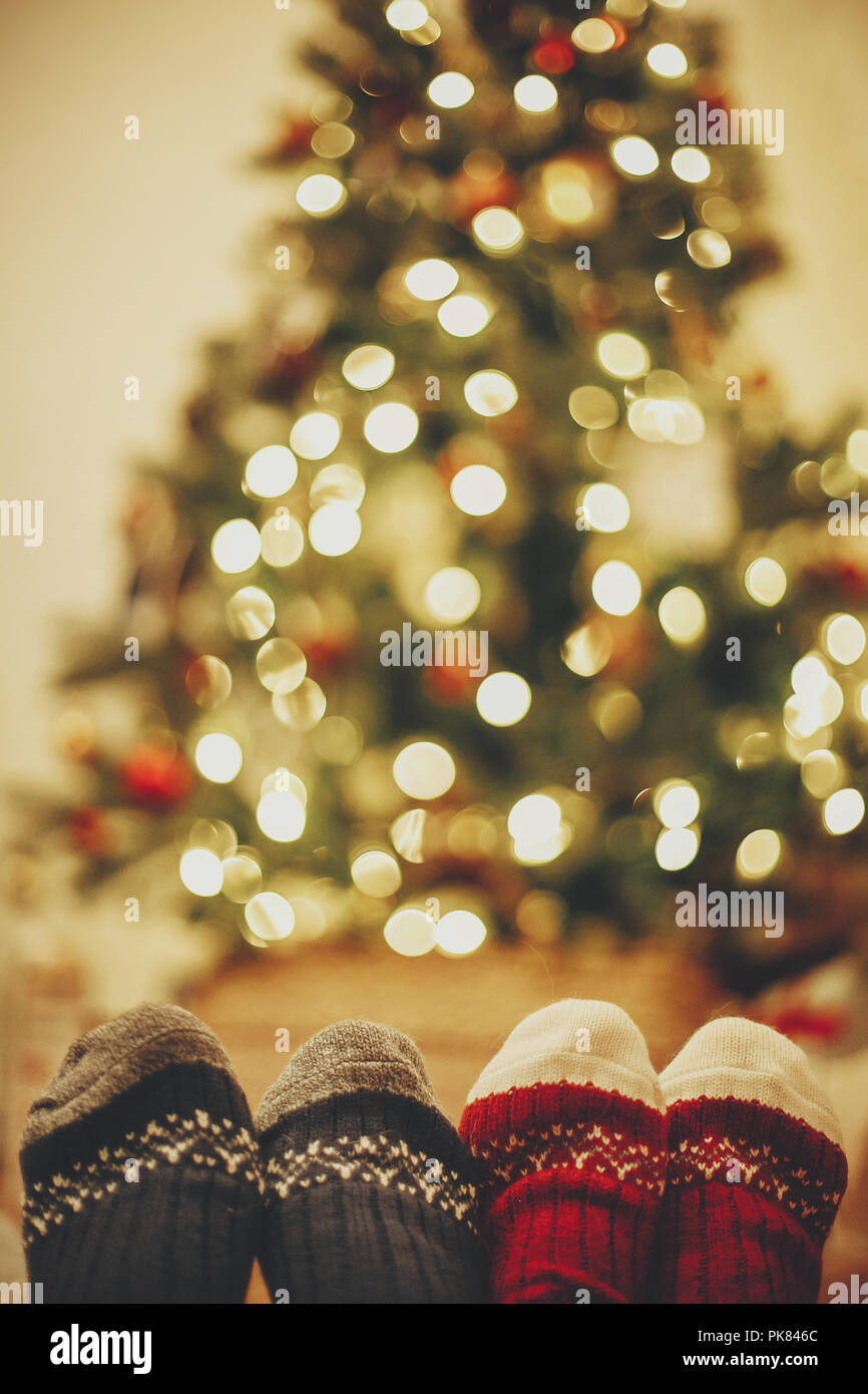 stylish festive socks on couple legs on background of golden beautiful christmas tree with lights in festive room family relax time cozy winter holi