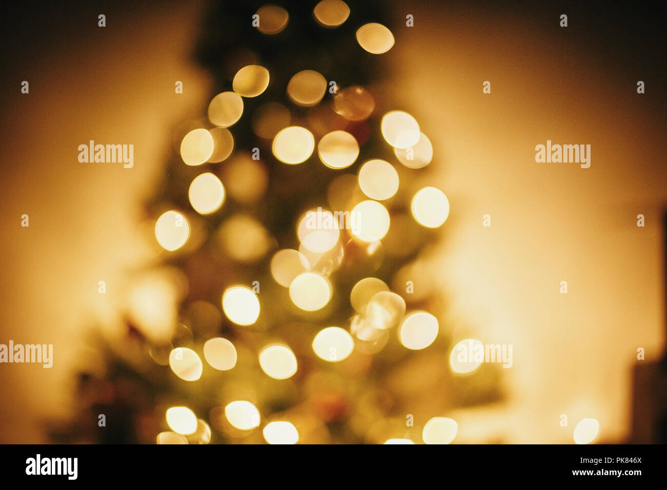 beautiful christmas tree golden lights in festive room. christmas abstract background,  blur defocused bokeh of yellow glowing decoration on christmas - Stock Image
