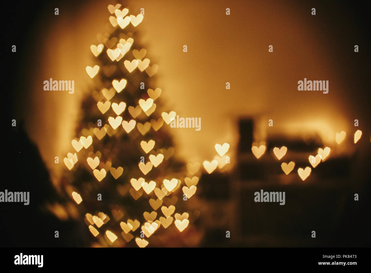 christmas abstract background, beautiful christmas tree golden lights hearts bokeh. blur of yellow glowing illumination in festive room. decor for win - Stock Image