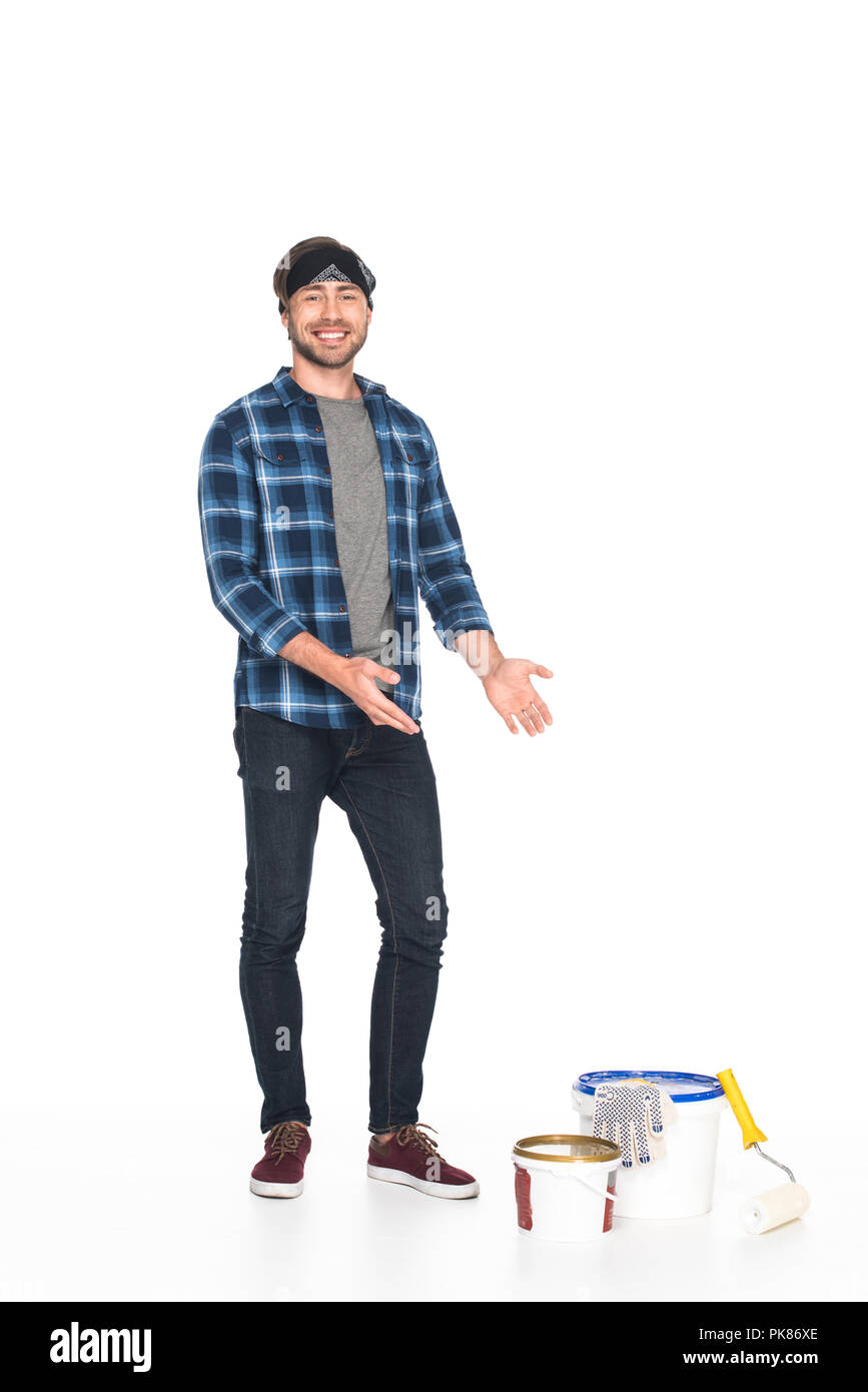 man in headband pointing by hands on paint tins, paint roller and protective gloves isolated on white background - Stock Image