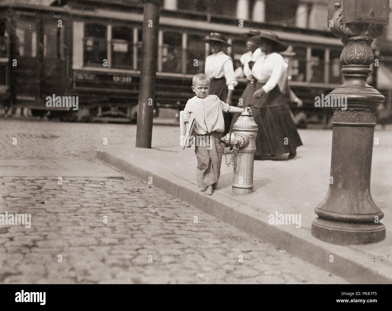 Child newspaper vendor, New York.  Taken 1909.  After a photograph by Lewis Hine, 1874-1940.  Hine was a sociology teacher who used photography to record social problems and spur reform. - Stock Image