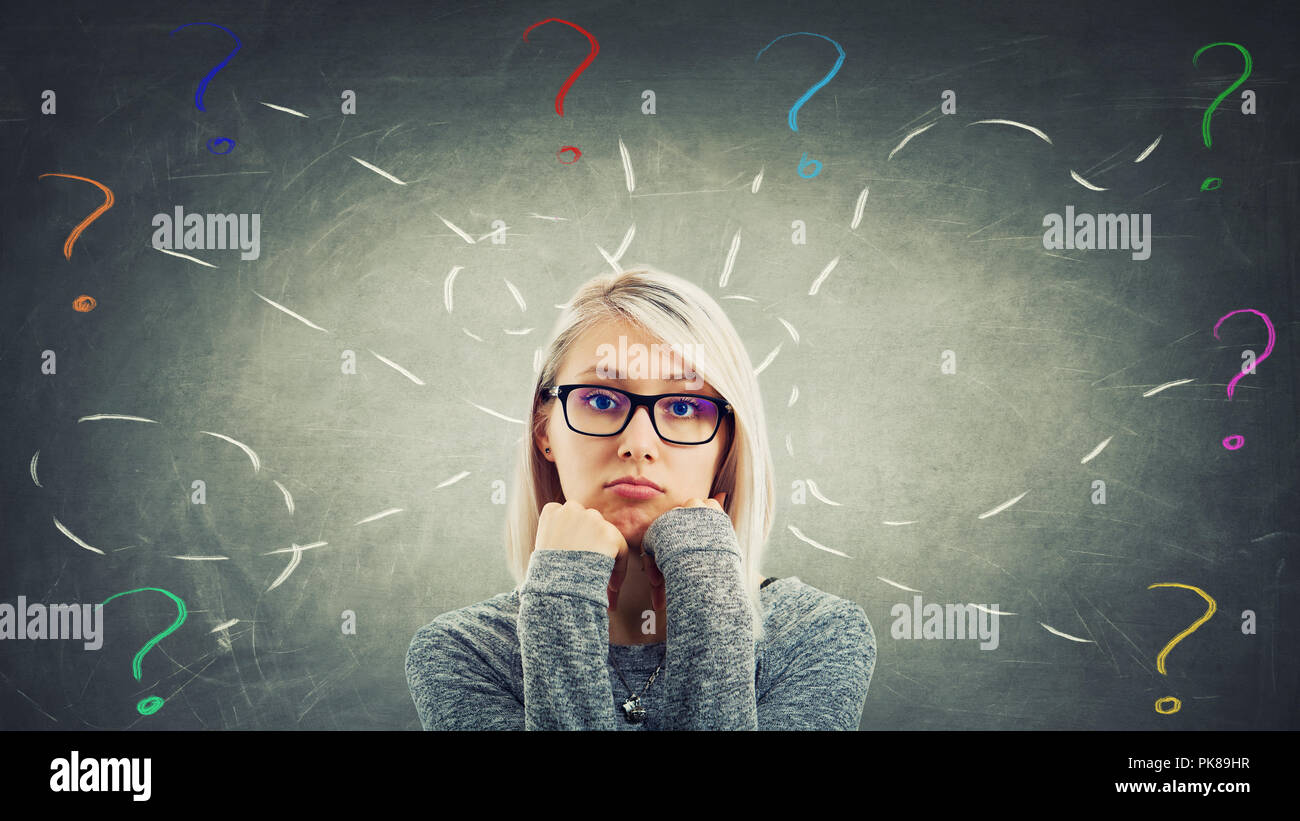 Puzzled and bored woman wearing glasses hold both hands under chin stand over blackboard background have a lot of questions as colorful interrogation  - Stock Image