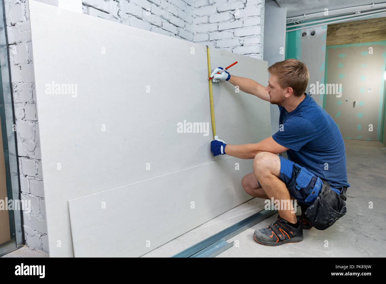 Man Measuring Plasterboard Sheet For Interior Construction Stock Photo Alamy
