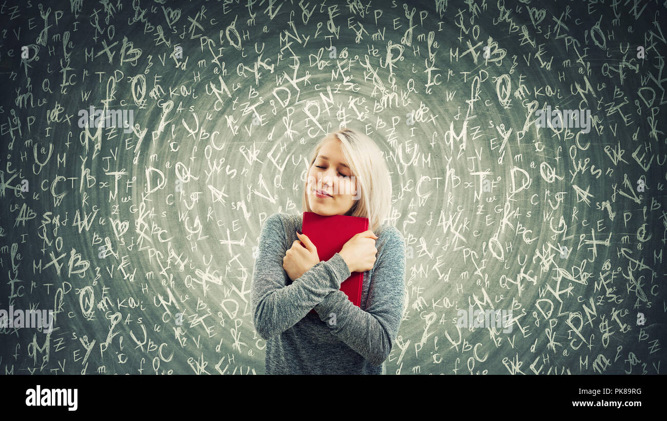 Young woman student holding a red book to chest with closed eyes. A warm hug show the love for knowledge and different letters flying around. Hypnotic - Stock Image