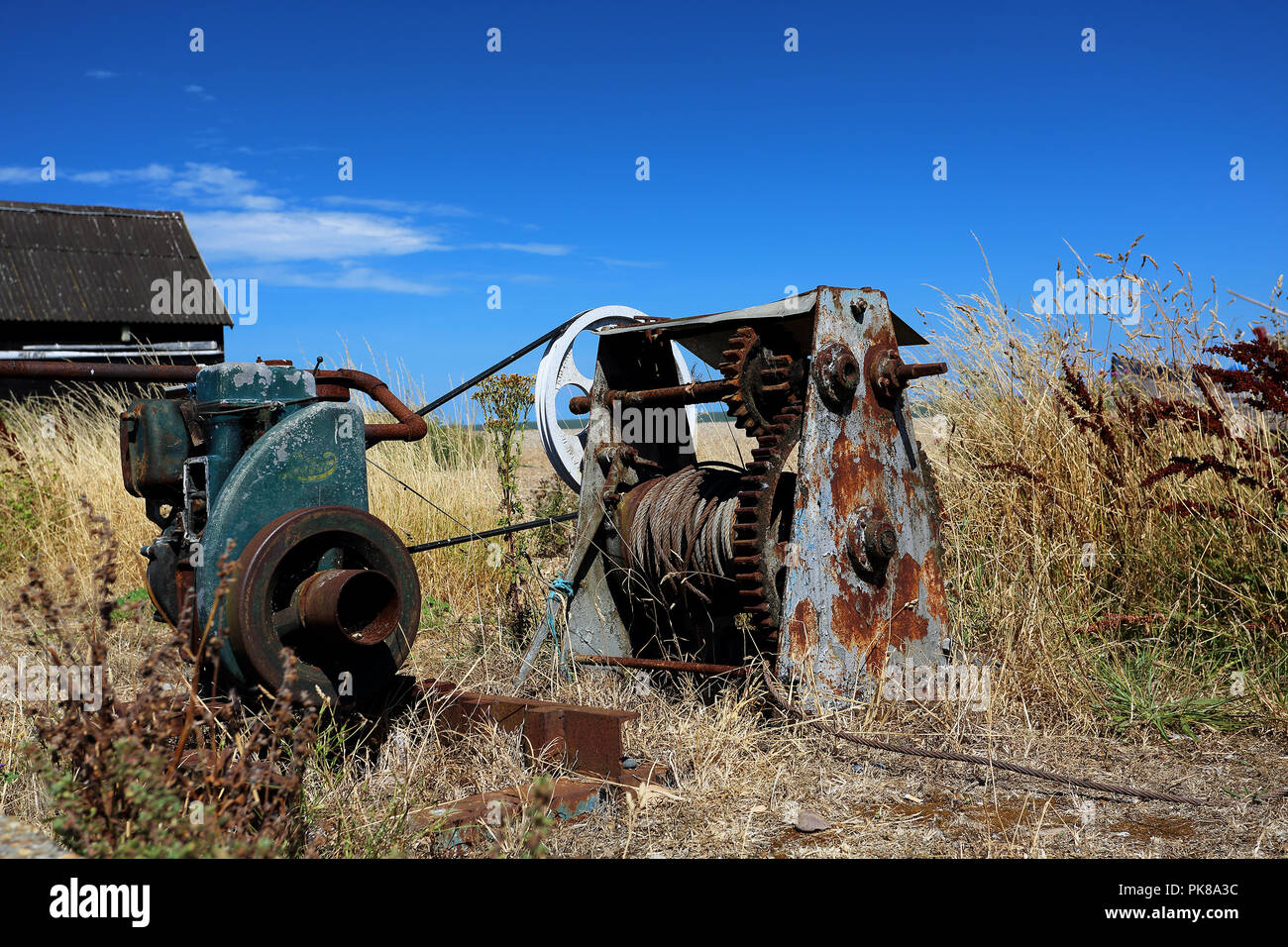 Redundant old winch machinery abandoned in a field next to the beach at Aldeburgh, Suffolk, UK - Stock Image