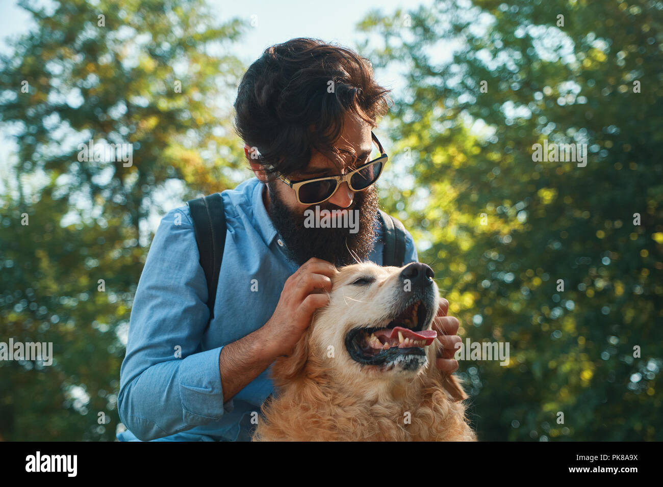 Man and dog having fun, playing, making funny faces while resting in the park. Life is beautiful, best friends concept. Stock Photo