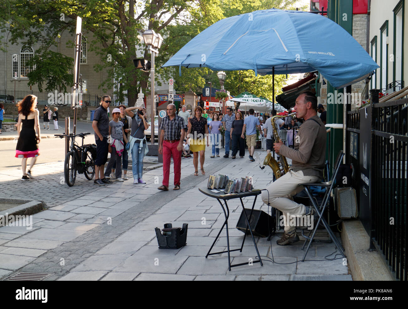 A busker playing a saxophone in the busy tourist area of Vieux Quebec in Rue Ste Anne, Quebec City, Canada - Stock Image