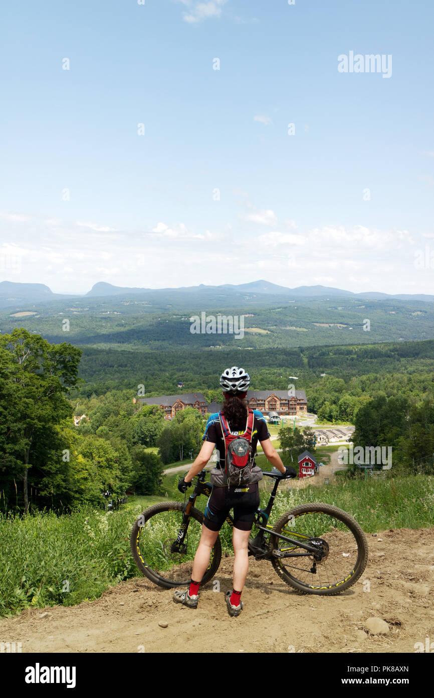 A lady mountain biker (in her 40s) pauses to admire the view on the Kingdom Trails mountain bike park in East Burke, Vermont, USA - Stock Image