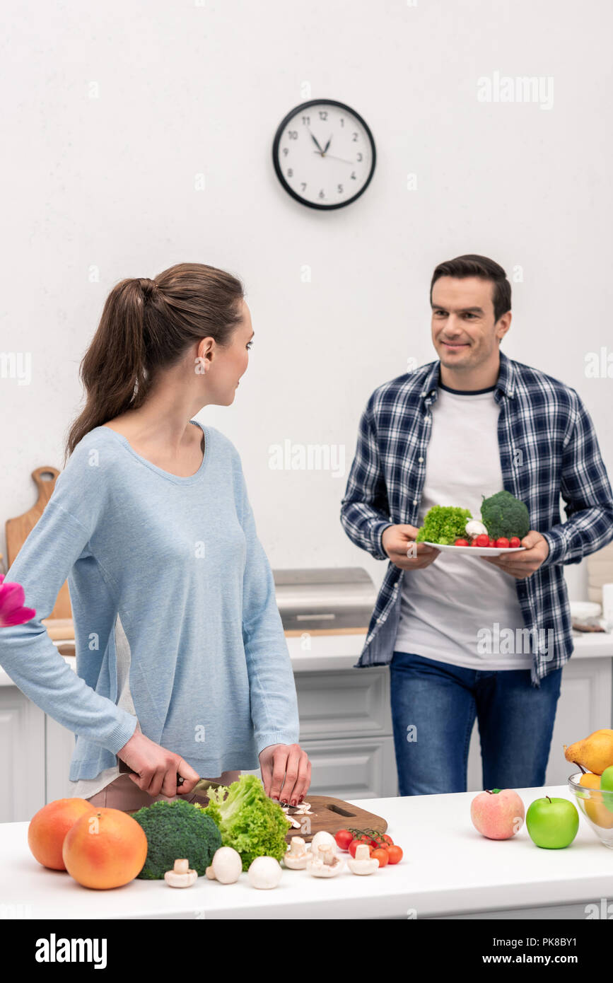 happy vegan couple cooking healthy dinner together - Stock Image