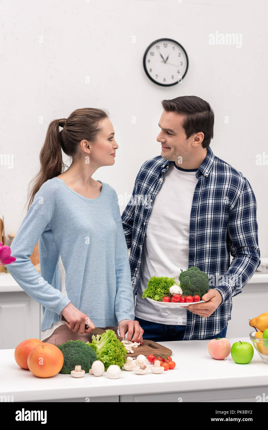 beautiful vegan couple cooking healthy dinner together - Stock Image
