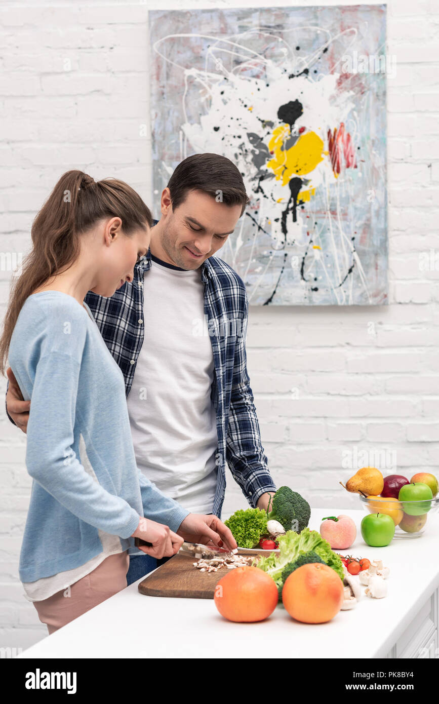 beautiful adult couple cooking healthy vegetarian dinner together - Stock Image