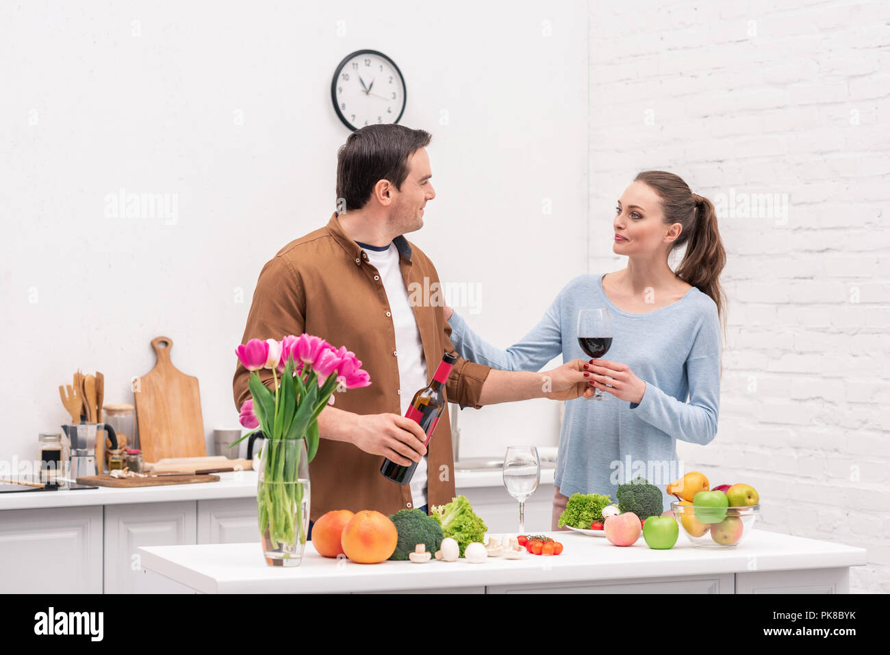 beautiful adult couple with red wine cooking together at kitchen Stock Photo