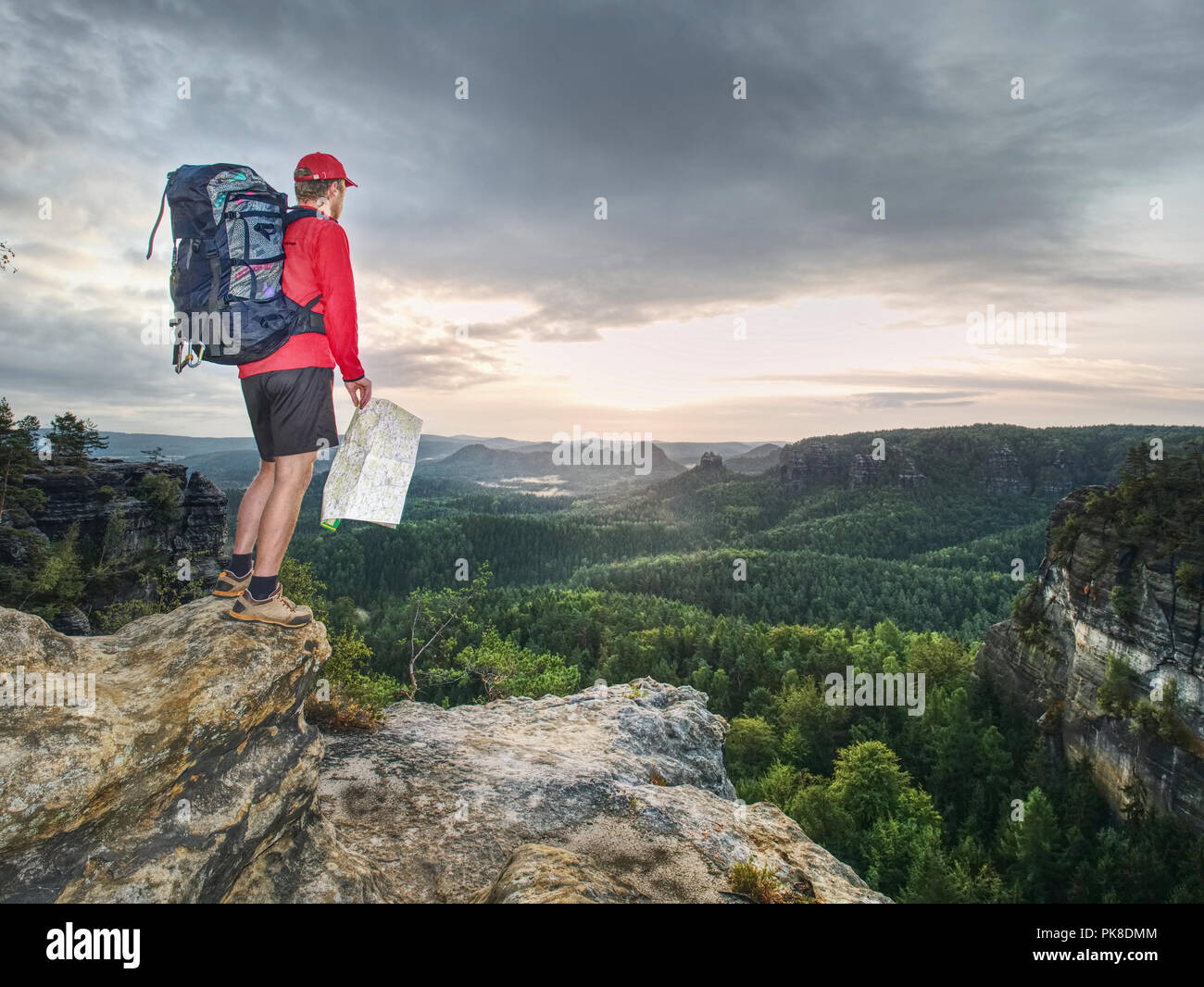 Sportsman with backpack on summit watch the paper map. Navigation in wild nature. Tourist in red jacket and black pants. - Stock Image