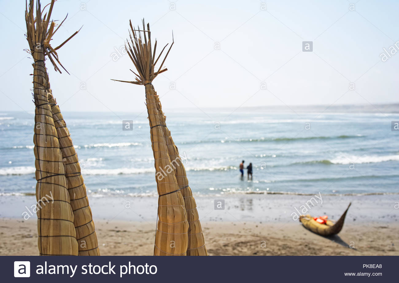 Reed boat Caballito de Totora on the beach in Huanchaco Trujillo Peru with a couple in the background who is out swimming - Stock Image