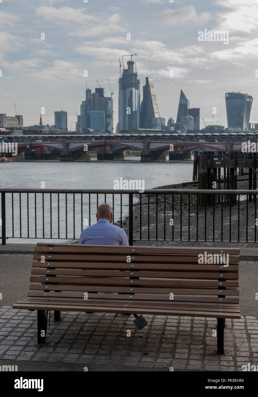 a man sitting on a wooden park bench on the south bank of the river thames in central London looking across the river towards the city of London. - Stock Image