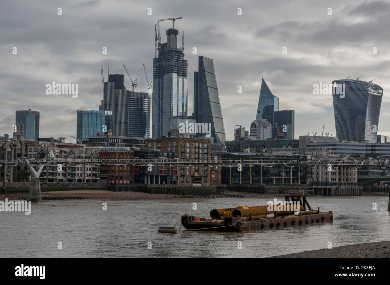 the city of London skyline on a grey and overcast day with a construction barge in the foreground. - Stock Image