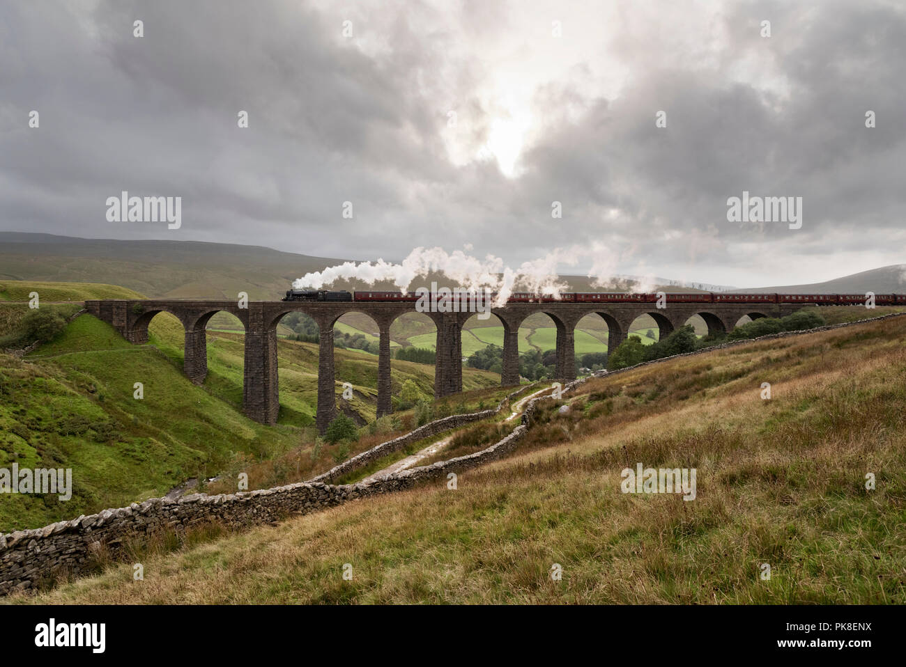 'The Cathedrals Express' crosses Arten Gill Viaduct in Dentdale in the Yorkshire Dales National Park. It is hauled by a Stanier 8F steam loco of 1942. - Stock Image