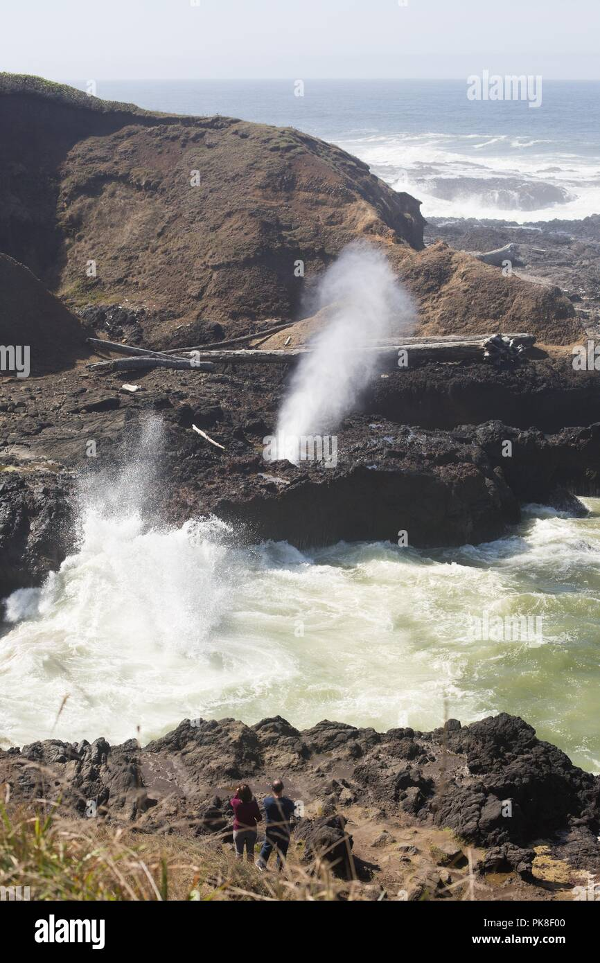 A couple looking at the Spouting Horn at Cape Perpetua in Oregon, USA. - Stock Image