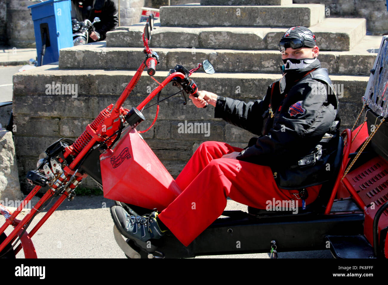 Corfe, England - June 03 2018: Mean looking biker on a chopper trike motorcycle, wearing black and red, with bandanas covering his head and face - Stock Image