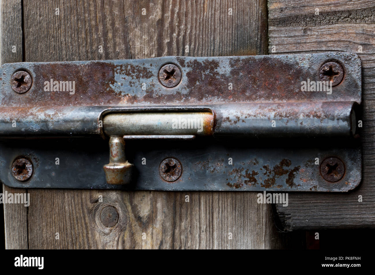 Old rust outdoor bolt lock on a wooden fence. - Stock Image