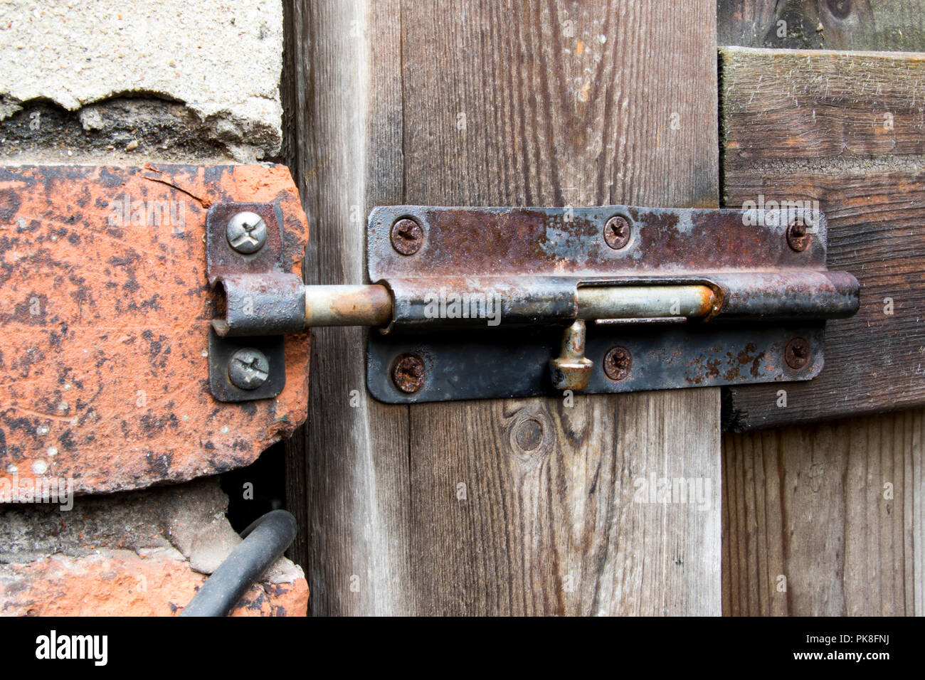 Rusty gate lock. Wood fence gate and house brick close up. - Stock Image