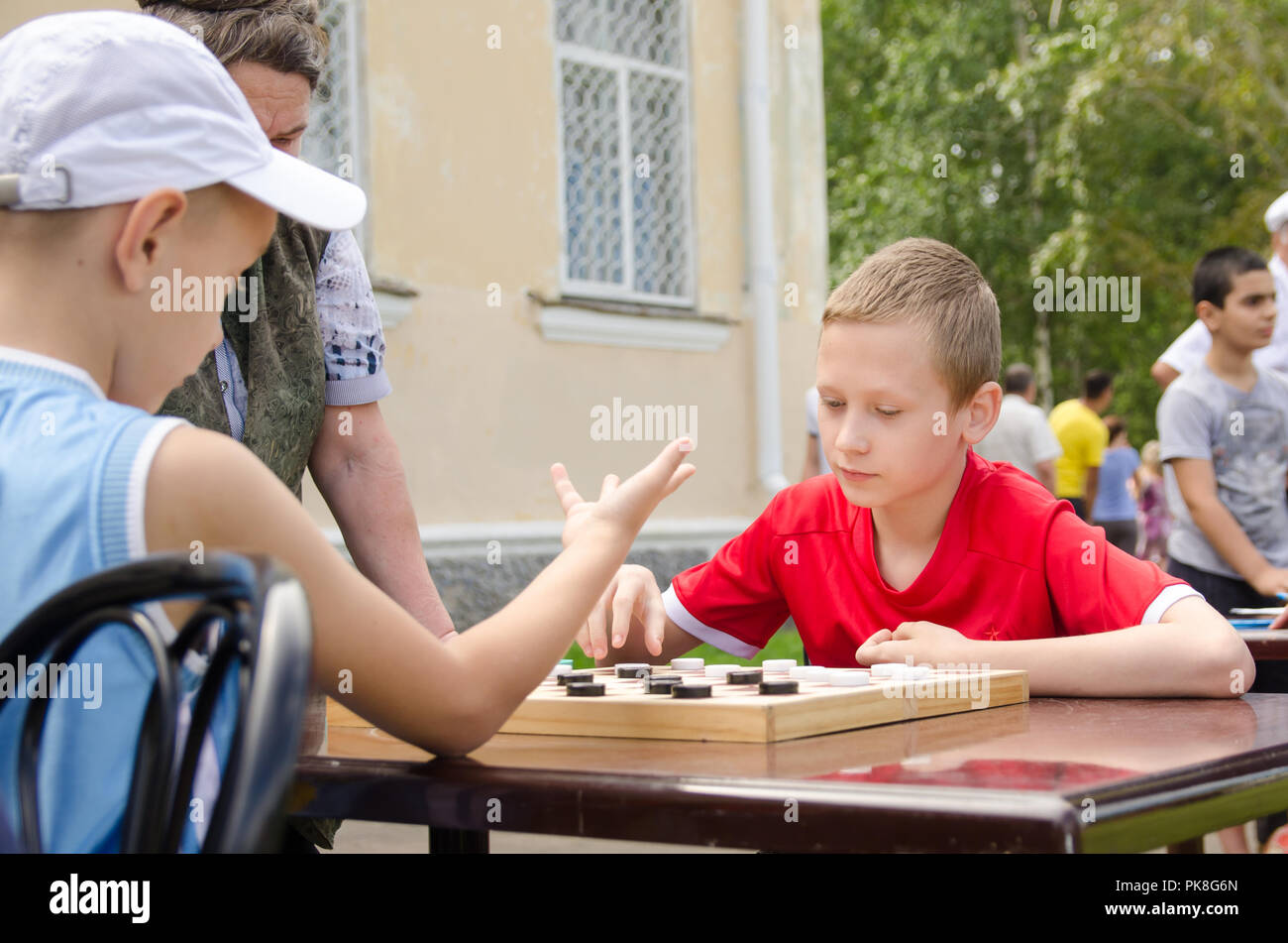 Komsomolsk-on-Amur, Russia - August 8, 2016. Public open Railroader's day. two boys play checkers in park. amateur competitions Stock Photo