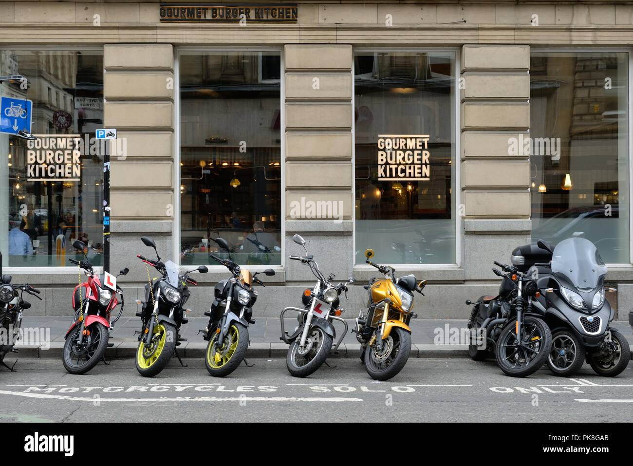 A row of motorbikes parked outside the Gourmet Burger Kitchen in Glasgow city centre, Scotland, UK - Stock Image
