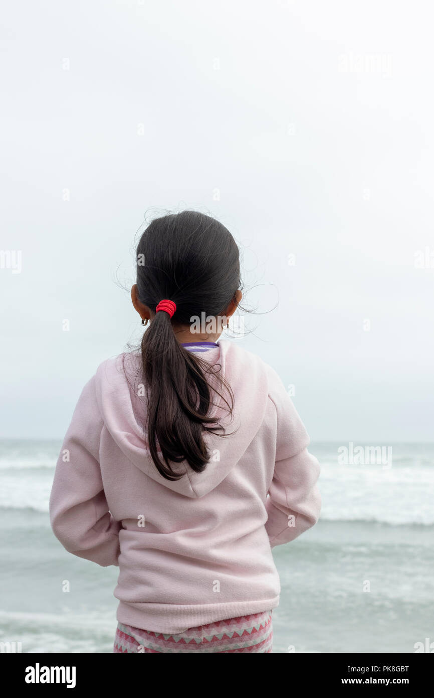 Little girl observing the calm sea - Stock Image