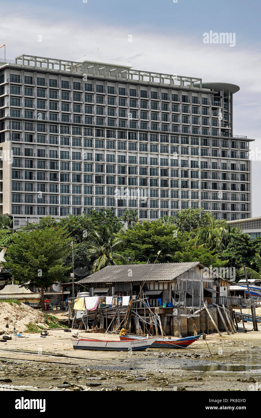 Contrasting lifestyle of a luxury high rise apartment complex dwarfing the poorer beach shack. Thailand Southeast Asia - Stock Image
