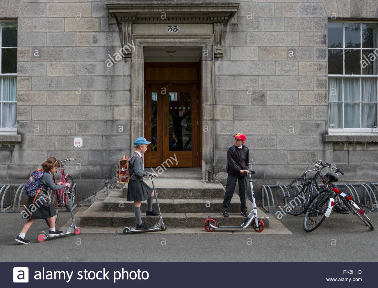 Three young children wearing school uniforms riding scooters stopped in front of House 33 on the Trinity College, Dublin, Leinster, Ireland - Stock Image