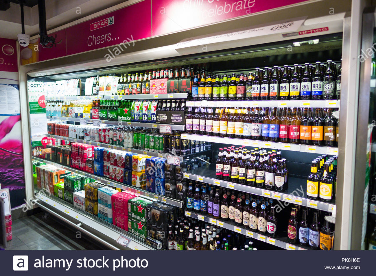 Large selection of refrigerated beer in bottles and aluminum cans on sale in Spar convenience retail shop, Merrion Row, Dublin, Leinster, Ireland - Stock Image