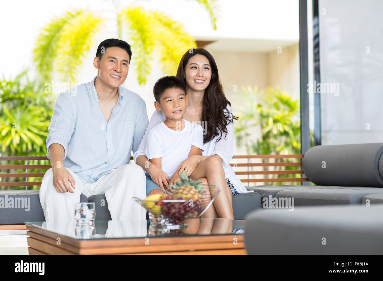 Happy young family sitting on the sofa - Stock Image