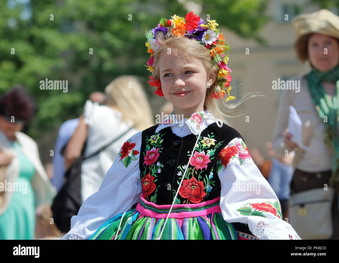 Young blon-haired Slavic girl from Lowicz reggion, Poland, dressed in traditional colorful folk costumes during annual Corpsu Christi procession. - Stock Image