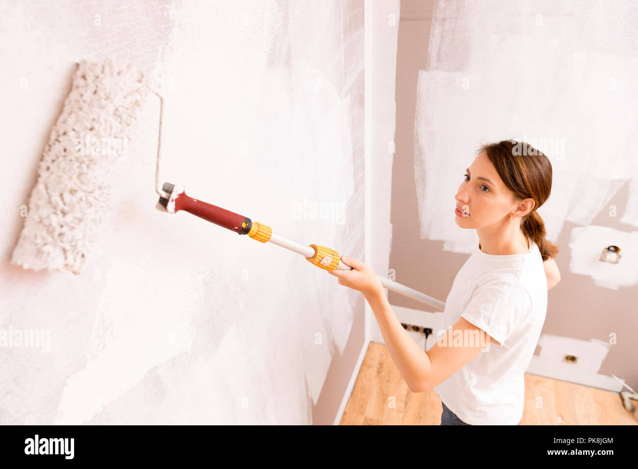 Home improvement. Beautiful woman painting wall with paint roller. - Stock Image