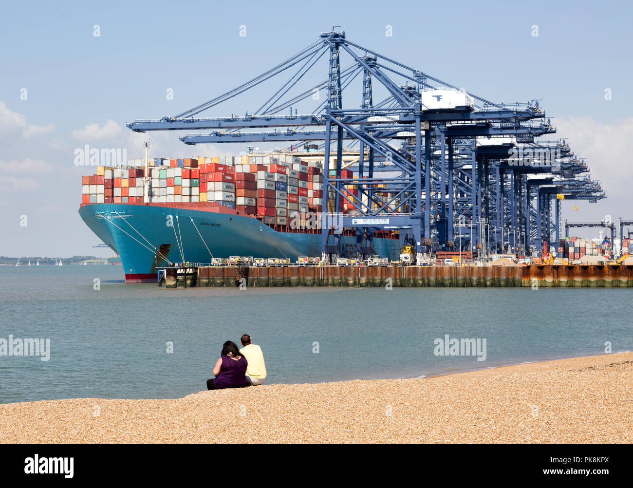 People sitting on beach as cranes load Edith Maersk container ship, Port of Felixstowe, Suffolk, England, UK - Stock Image
