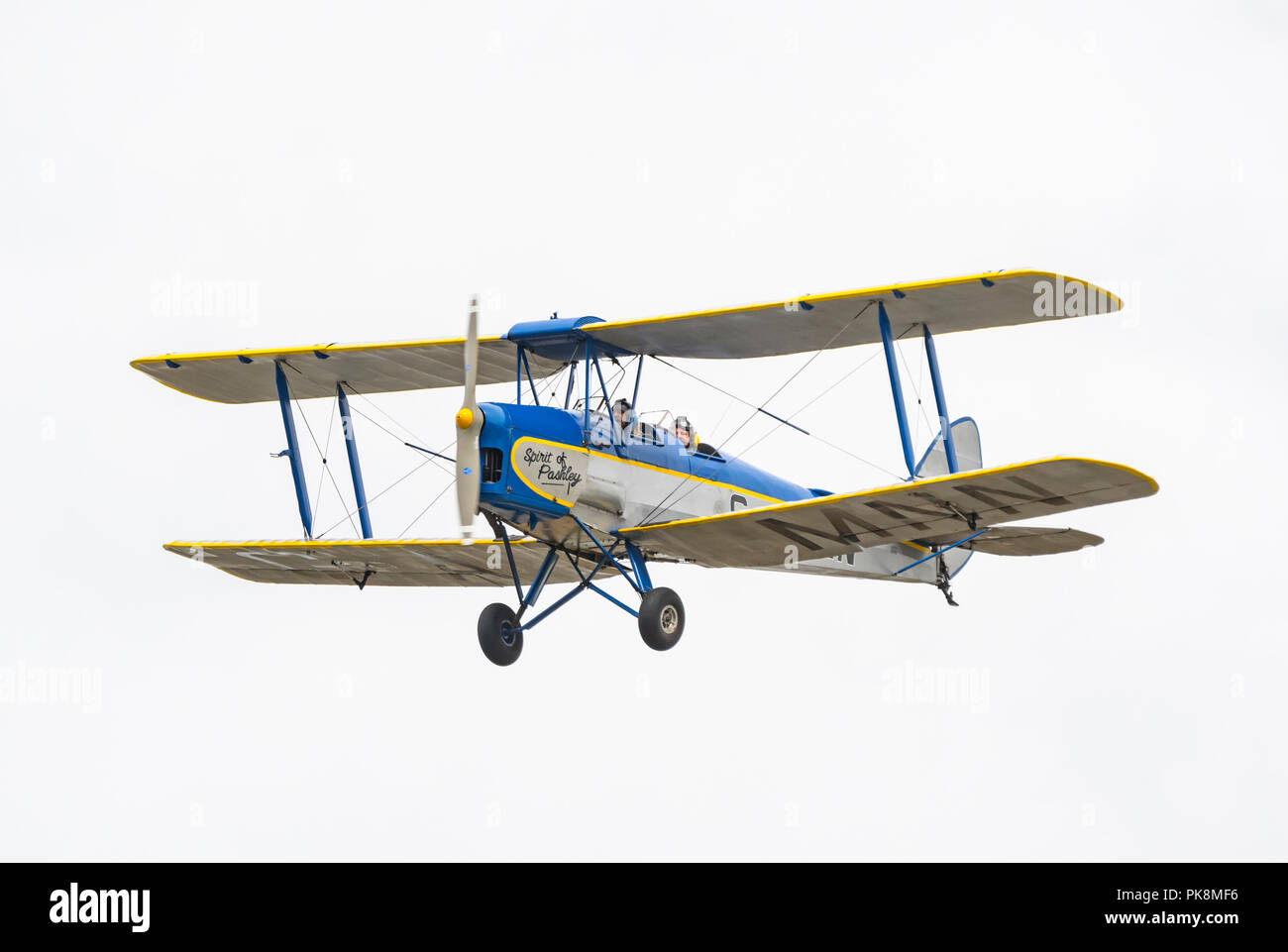 Spirit of Pashley, G-AMNN, a 2 seater single engine Tiger-Moth Bi-plane flying on a dull day in Southern UK. - Stock Image