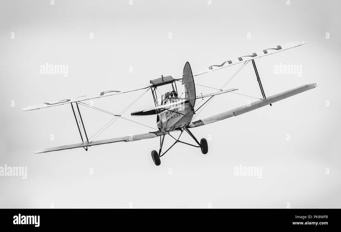 Spirit of Pashley, G-AMNN, a 2 seater single engine Tiger-Moth Bi-plane, rear view, flying away, in the UK. B&W monochrome. - Stock Image