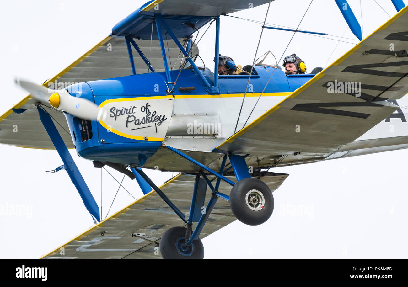 Spirit of Pashley, G-AMNN, a 2 seater single engine Tiger-Moth Bi-plane flying low as it comes into land in Southern UK. - Stock Image