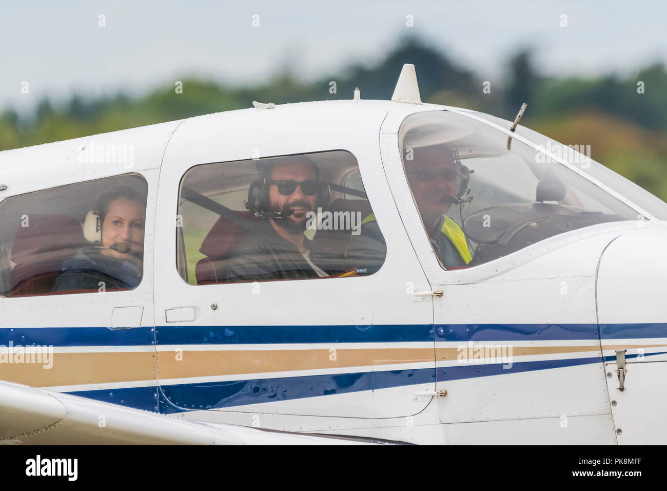 Small group of people sitting in a single engine private aircraft looking out the window smiling, ready to take off, in the UK. Private pilot. - Stock Image
