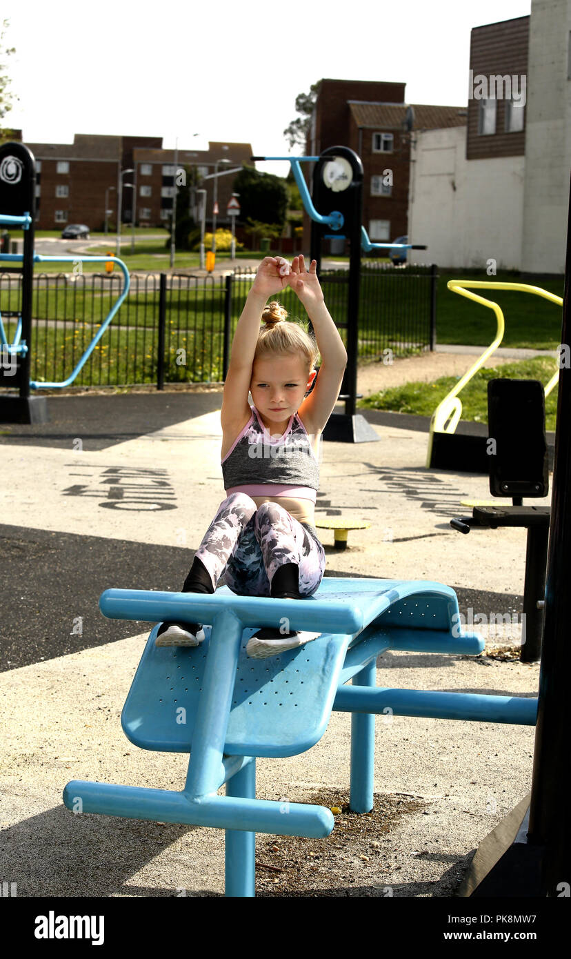 A Six Year Old Girl Doing Sit Ups On Free To Use Equipment In An Outdoor Fitness Area