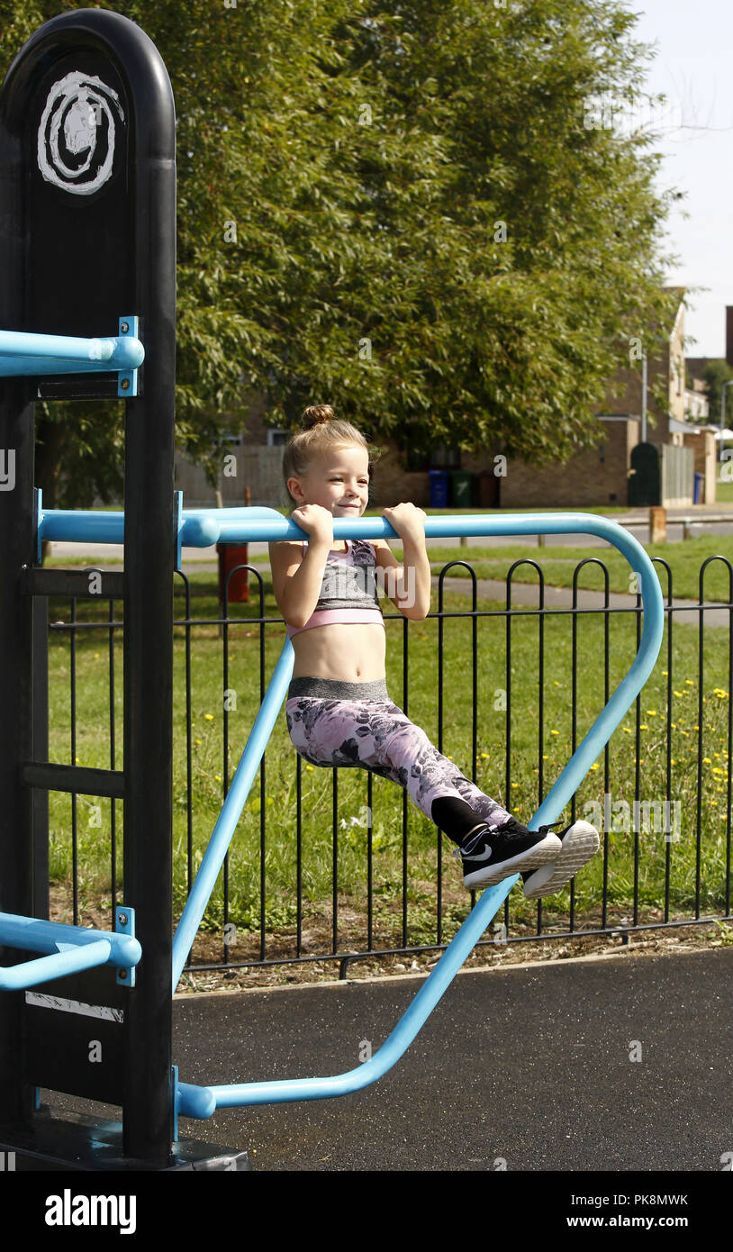 A Six Year Old Girl Doing Pull Ups On Free To Use Equipment In An Outdoor Fitness Area