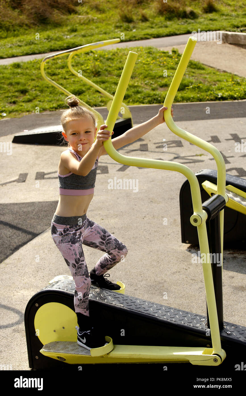 Six Year Old Girl On A Cross Trainer Machine In A Free To Use Outdoor Fitness Area