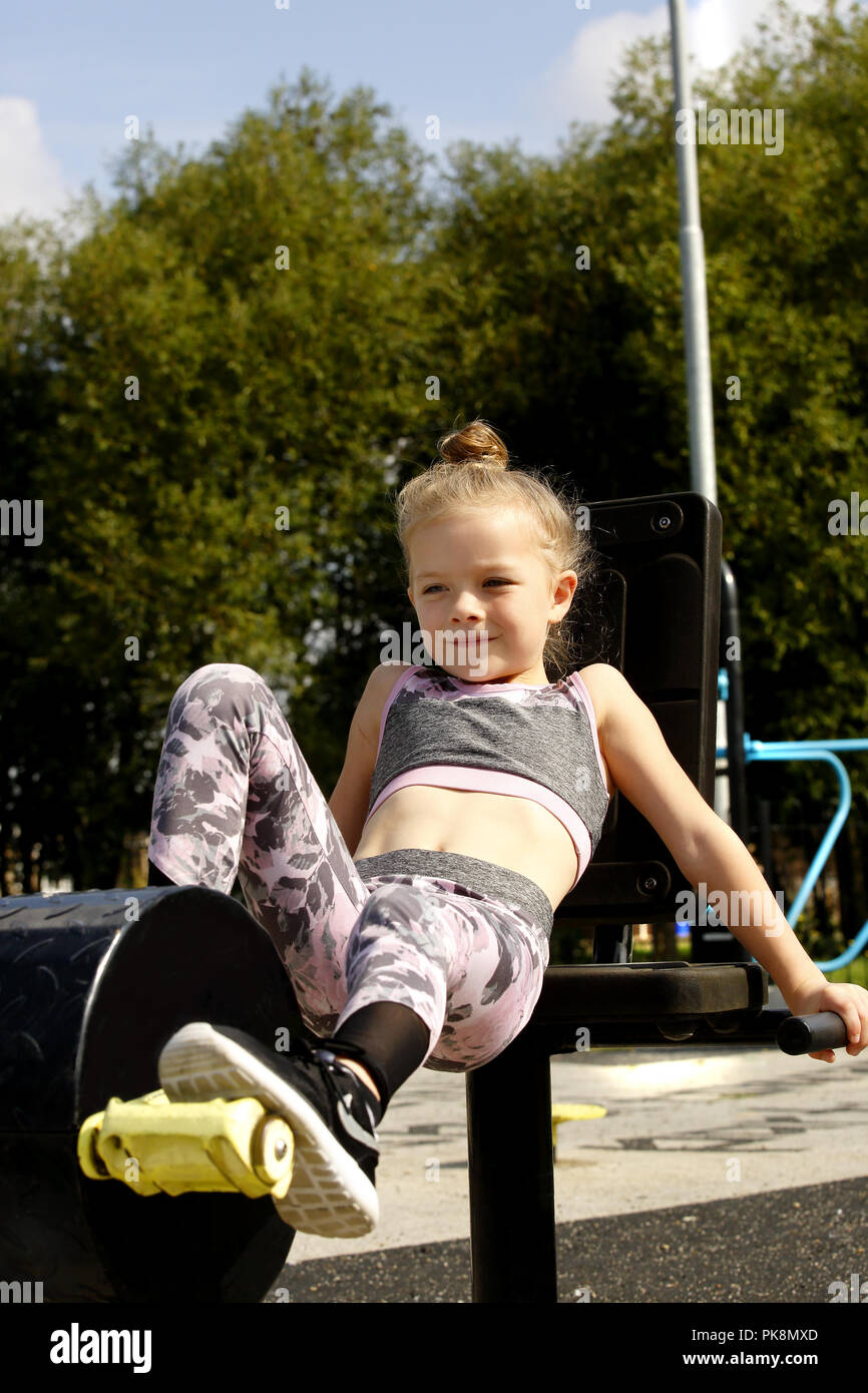 A Six Year Old Girl Just Managing To Reach The Pedals Of A Cycling Machine In A Free To Use Outdoor Fitness Area