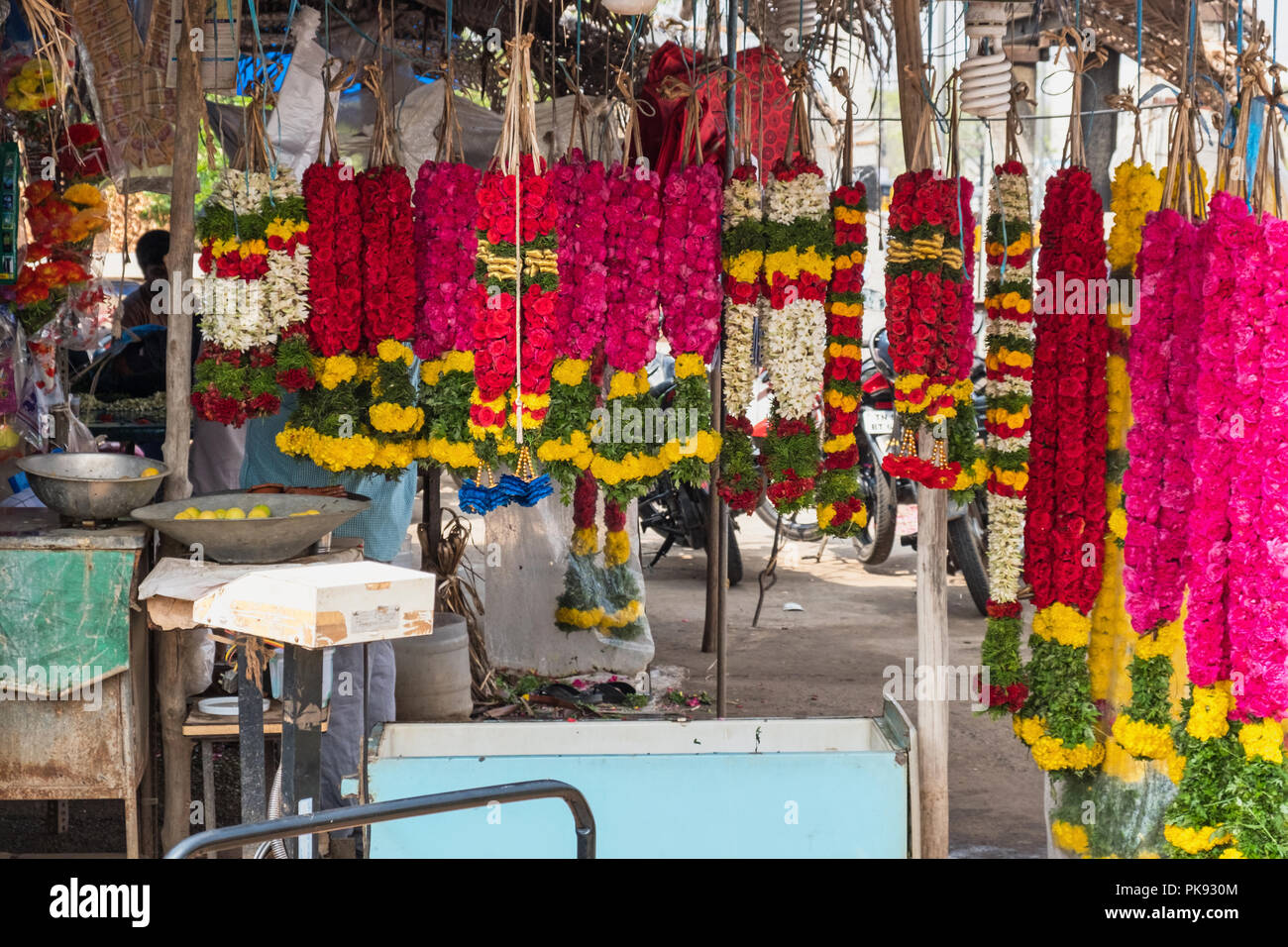 Colourful garlands for sale in an Indian flower market. They are widely used for dedications in Hindu rituals and for decorating festive occasions - Stock Image