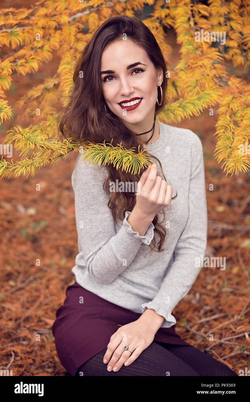An attractive smiling woman sitting on the ground as she poses for the camera holding a pine needle twig - Stock Image